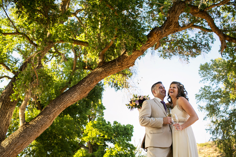 Bride and Groom laughing under the trees