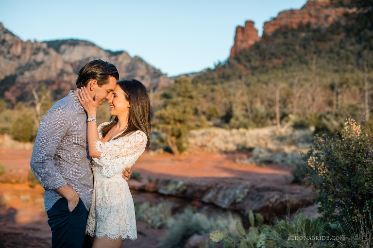 A couple snuggles with the red rocks behind them during their engagement session in Sedona
