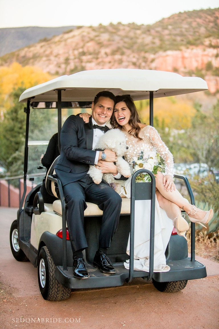 Bride and groom sit on the back of a golf cart with their puppy as they are driven back to L'Auberge from the Spirit Song Terrace where they were married.
