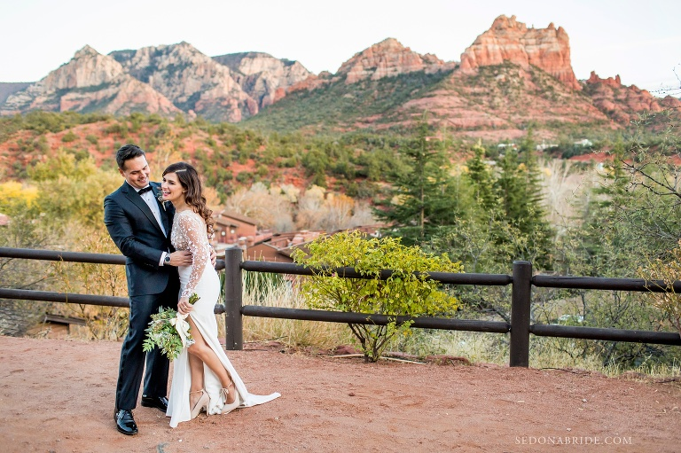 Bride and groom hold each other on their wedding day at L'Auberge with the red rocks and snoopy rock in the back ground