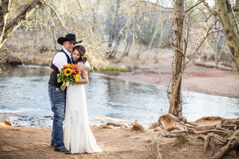 Groom wearing a cowboy hat hugs his bride with a sunflower bouquet at Red Rock Crossing with Oak Creek in the background