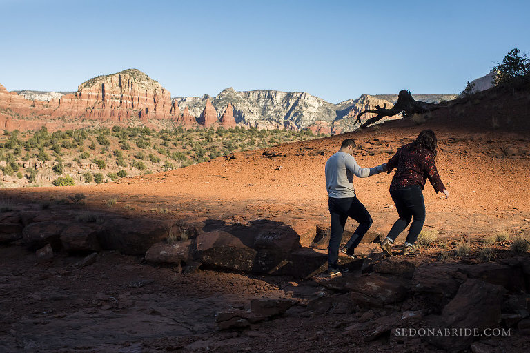 A couple walks holding hands as they hike up red rocks during their engagement session