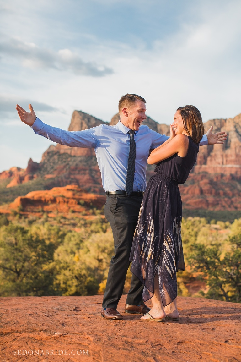 A man raises his hands with joy and a girl crying after a surprise proposal in Sedona