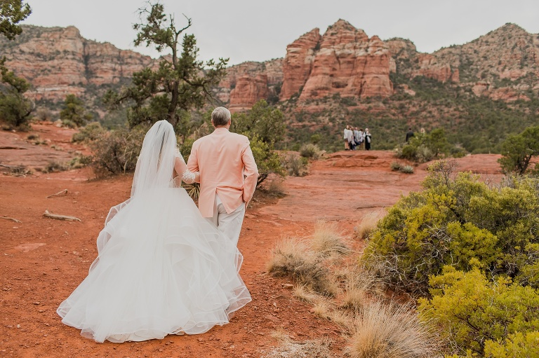 A wedding photo of a dad walking his daughter towards a wedding ceremony location on Bell Rock